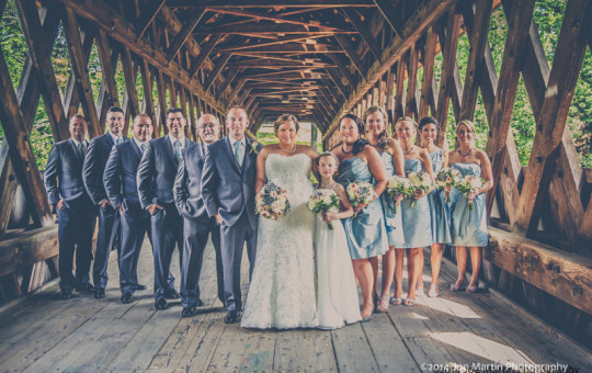 The bridal part posing for a photo in a NH covered bridge