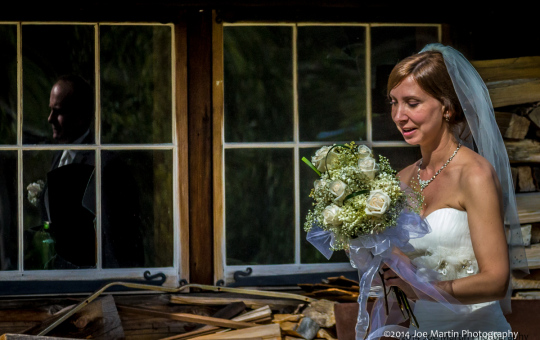 A bride walking after formal portraits with a reflection of the groom in the widows.