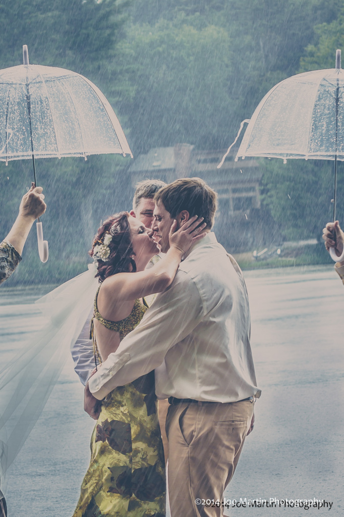 Raining hard this bride and groom kiss at this outdoor wedding
