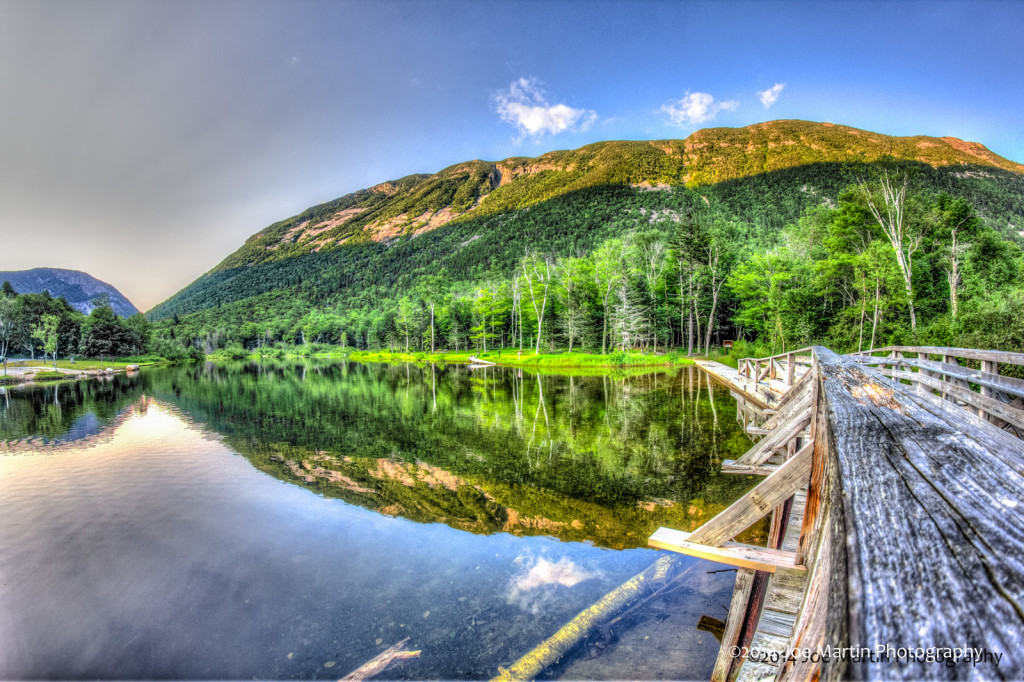 Reflection water shows this amazing old wooden bridge cross over to a large mountain