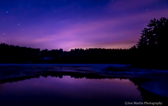 Purple sky over a melting pond at night