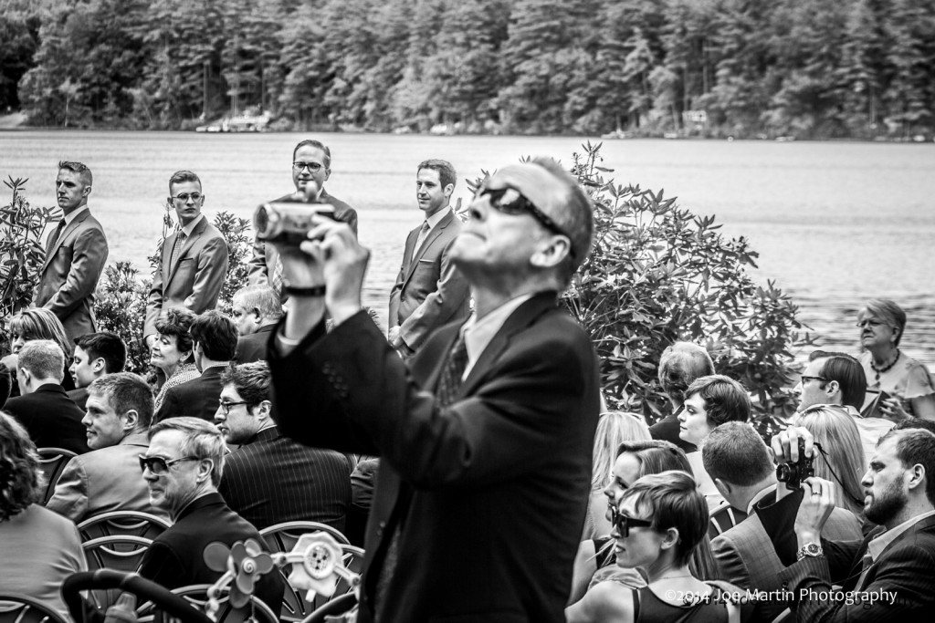 Black & white photo of a wedding guest that is taking a photo