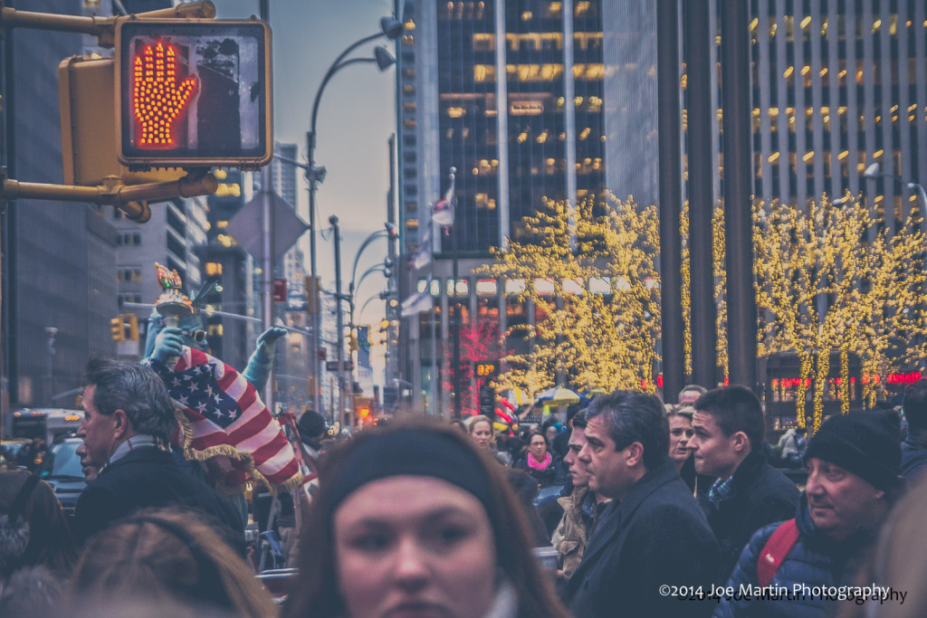 Images shows faces in a crowed street in NYC