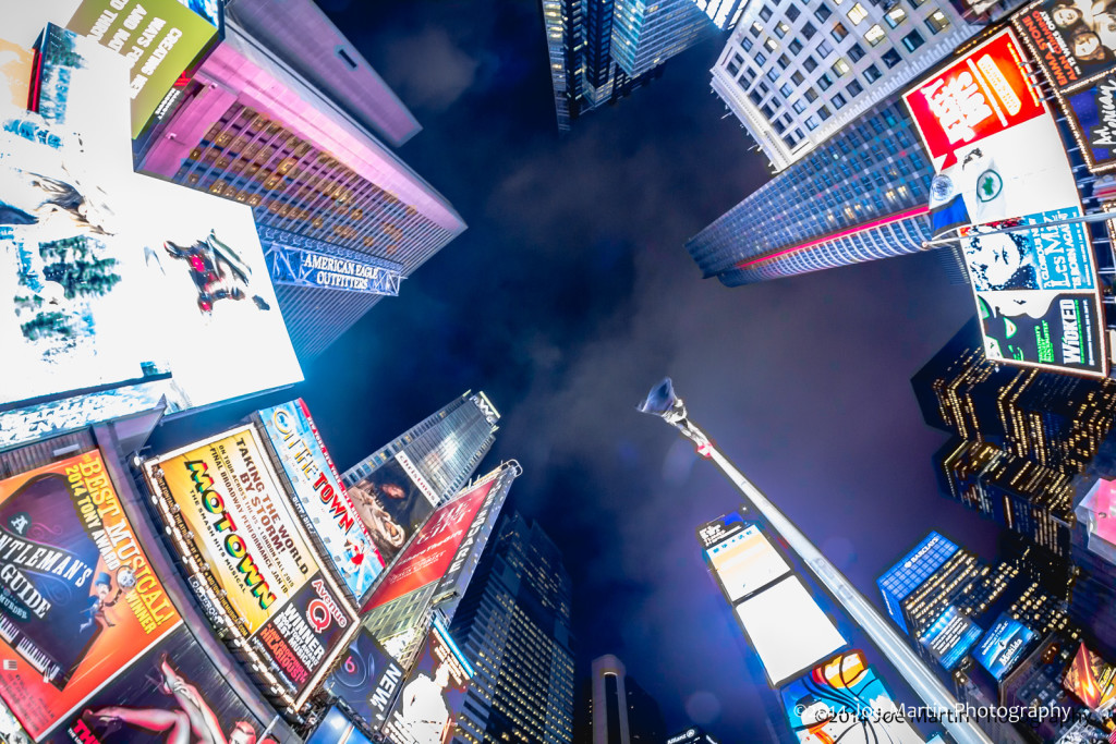 wide fish-eye photo looking up in the middle of time square many tall buildings scene