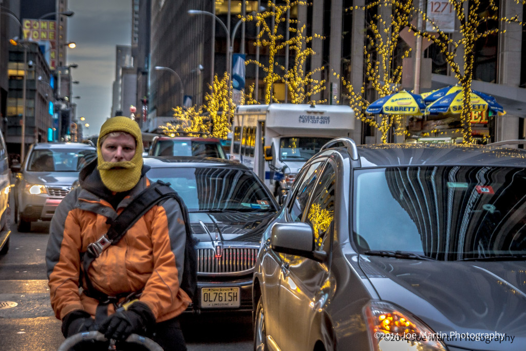street photo of a man at a red light with cold weather beard mask on. Looking right at me.