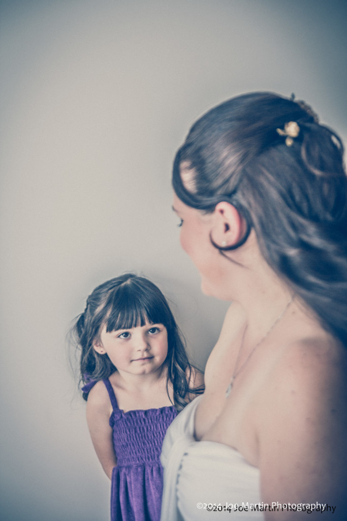 Little girl looking up at mom getting ready for her wedding.