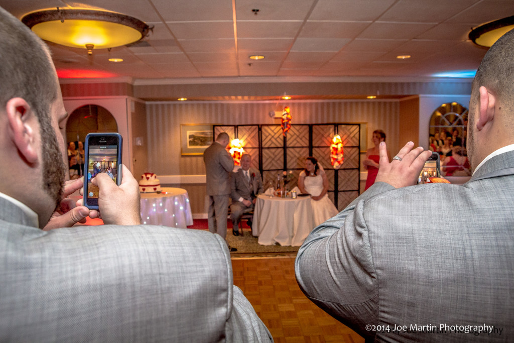 Photo of two groomsmen at wedding taking a photo of the bride and groom