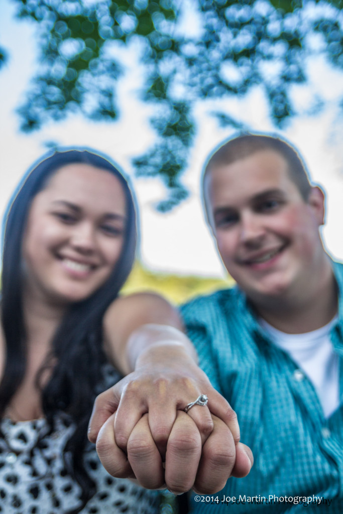 Couple shows engagement ring at a  photo shoot