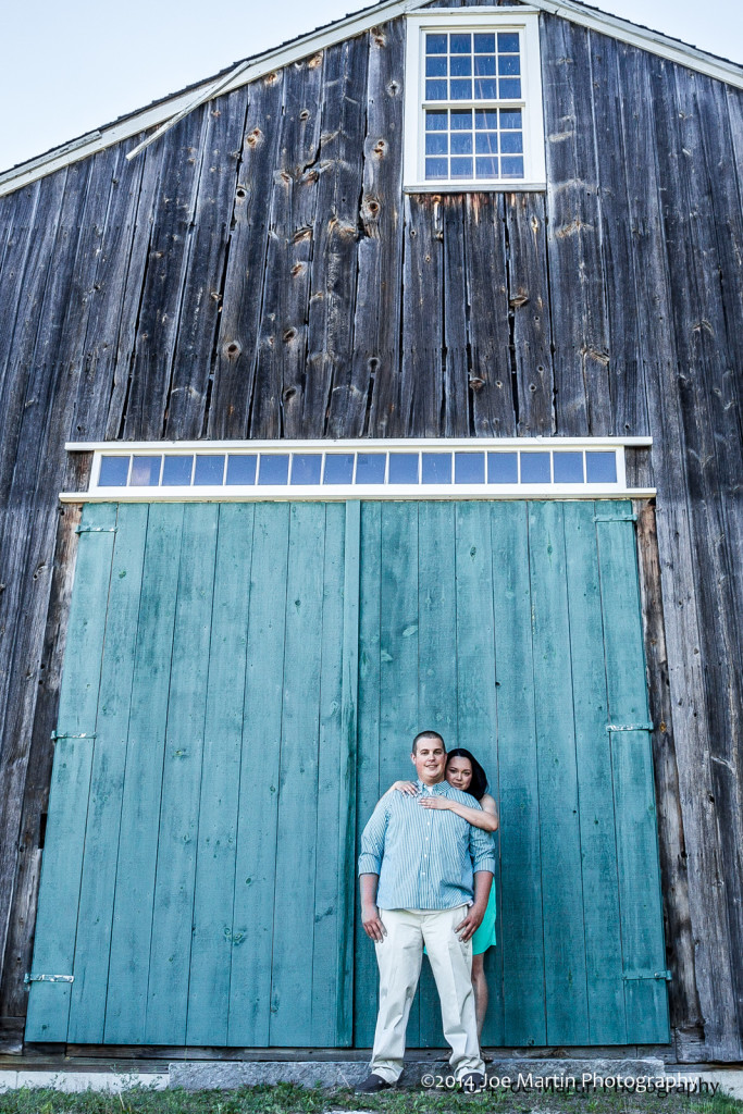 Engaged couple poses near an old barn in NH