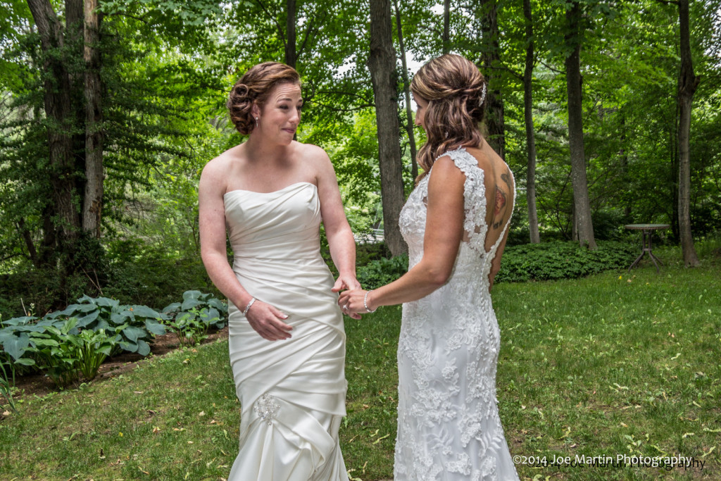 Two brides seeing each other for the first time at a gay wedding.