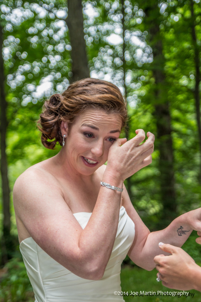 one bride wipes tears after seeing the other bride at this gay wedding.