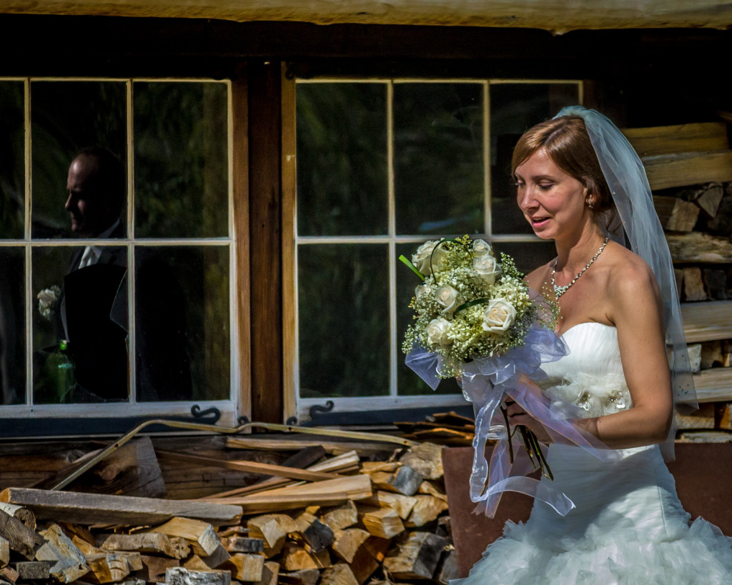 amazning wedding photo with a bride walking past windows, as her groom is seen in a reflection