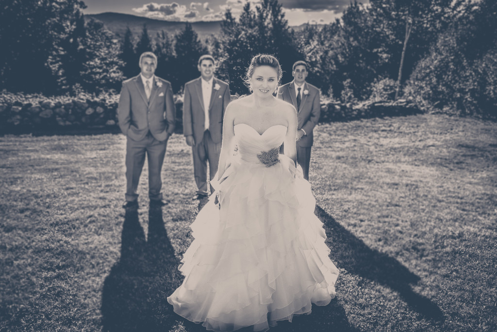 Black and white wedding photo in a field with Mountains as the backdrop. IN Maine