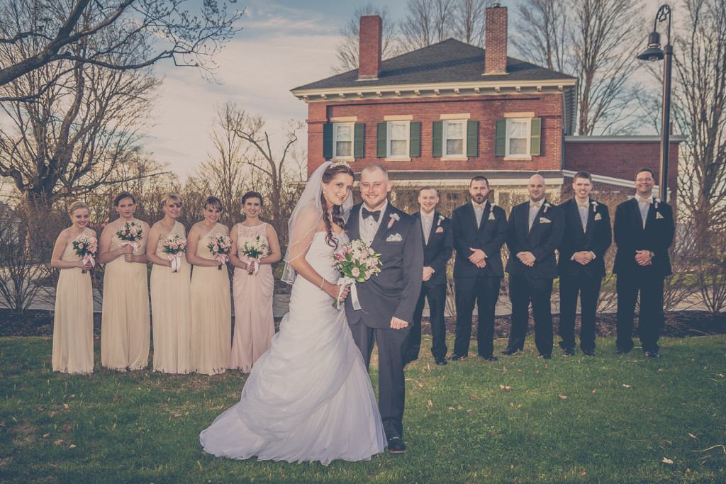 bridal party posing near a building with a vintage feel
