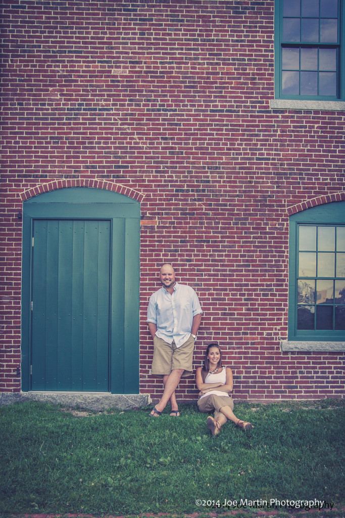 couple poses near a building in this  engagement photo