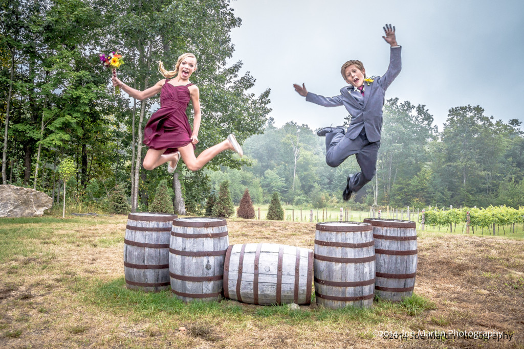 Two kids jumping off some wooden barrels this wedding photo
