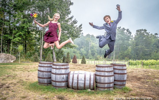 Two kids jumping off some wooden barrels at the Zorvino Vineyards