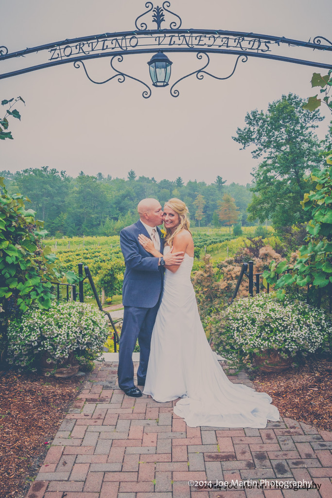 Married couple poses for a photograph near the garden entrance to the New Hampshire wedding venue Zorvino Vineyards