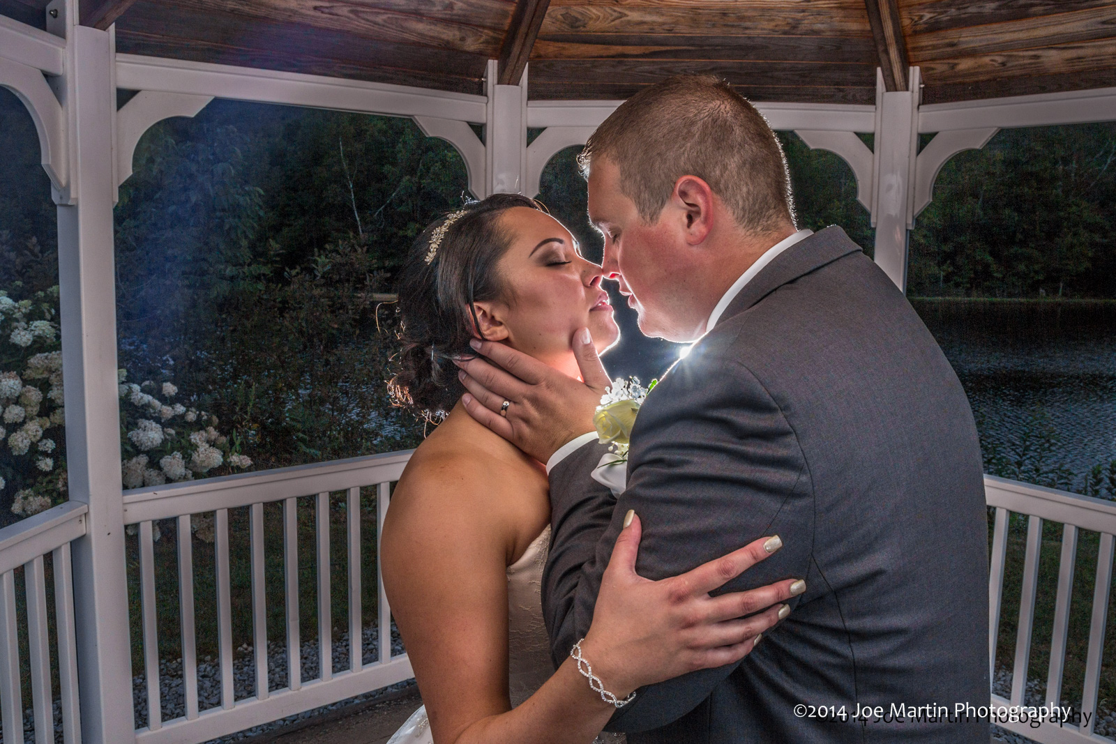 A bride is head lovingly by her husband in this wedding photo