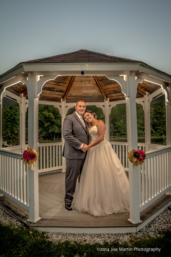Bride and groom posing in a gazebo after the wedding.