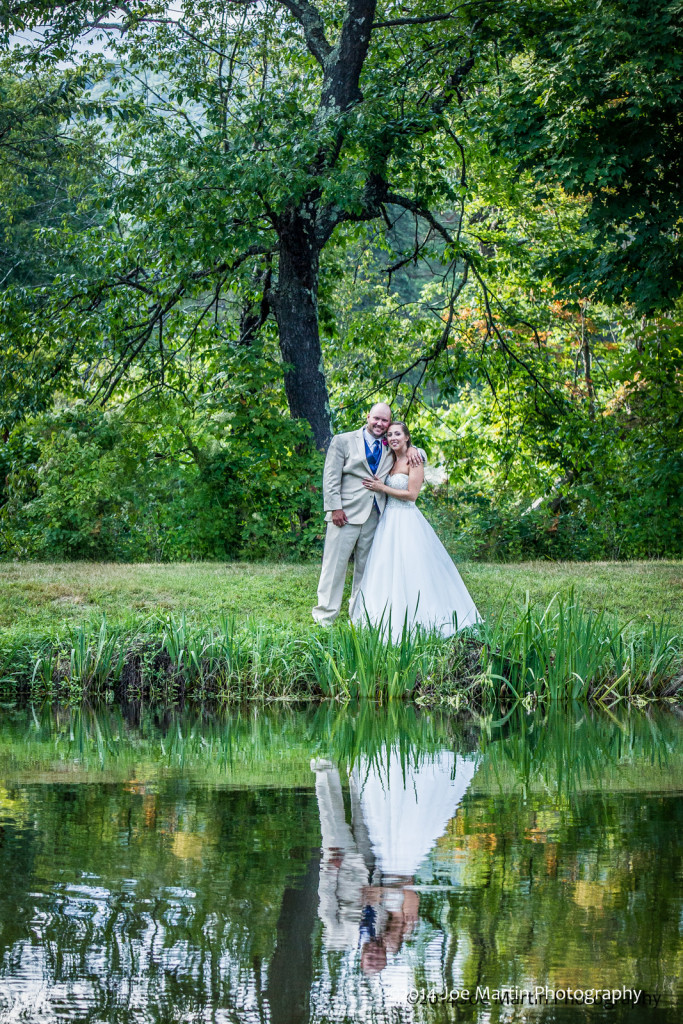 Bride and groom in a wedding photo with refection on the water.