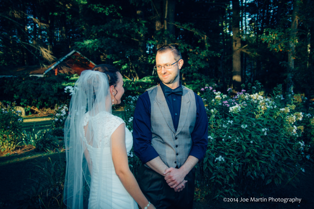 After turing around a groom smiles seeing his bride for the first time.