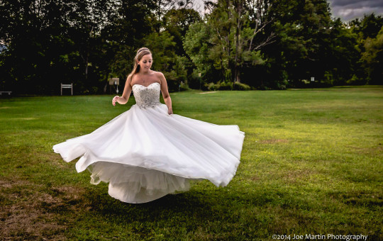 Photo showing a bride spinning her wedding dress