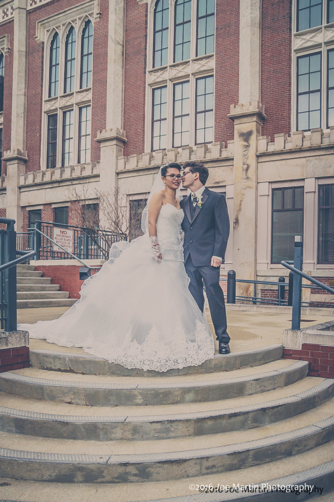Young wedding couple poses for a bridal portrait outside Manchester City Hall