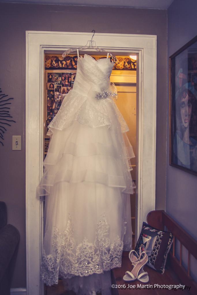 Wedding Dress hangs in a doorway