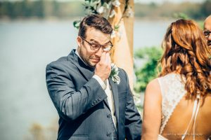 A groom wipes tears from his eye