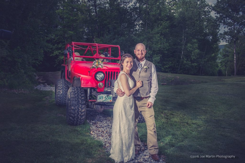 Wedding photo of couple with his red jeep