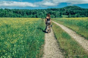 a bride walked on a dirt road in a field