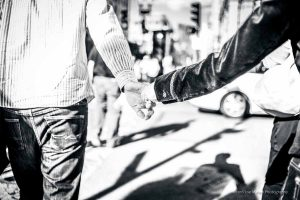 black and white photo of a couple holding hands  in the streets of boston