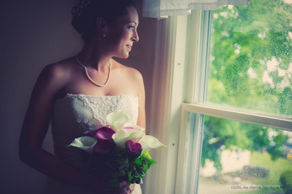 bride looks on the window on a rainy day wedding