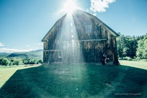 sun flair around a couple and a barn in this NH wedding photo