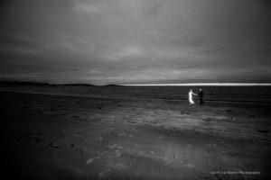 A wedding couple walks on the beach