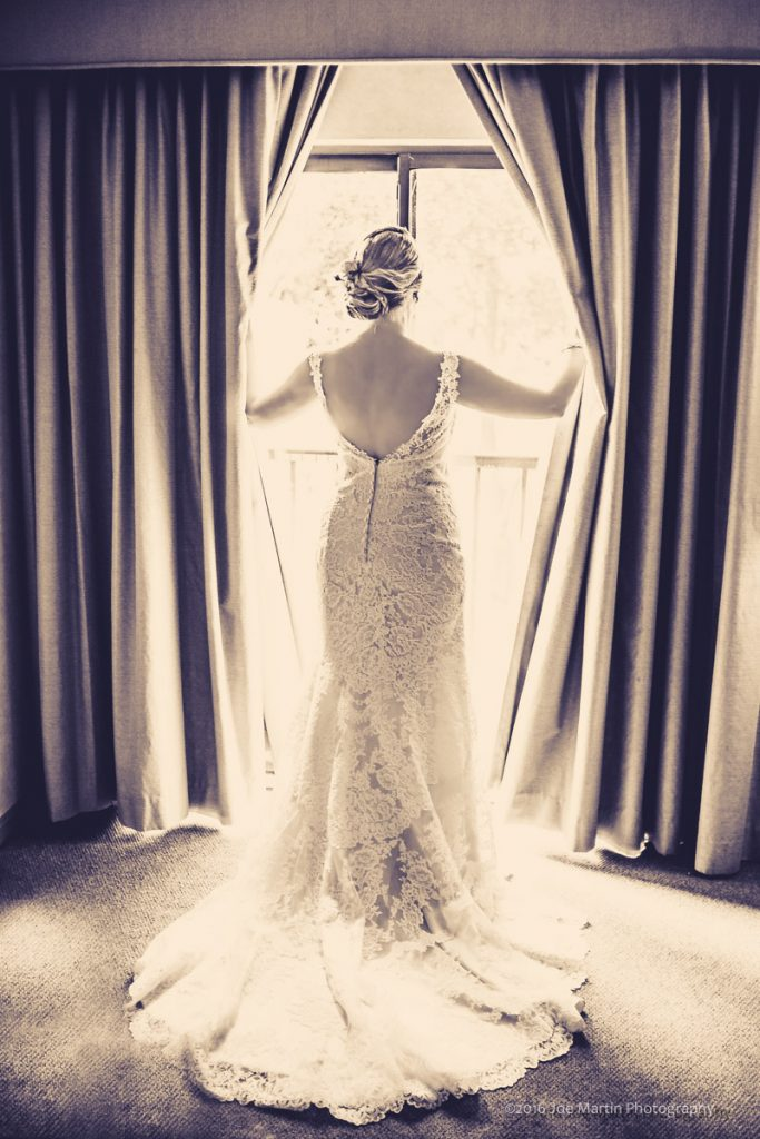 Bride opening the curtains in the bridal suite