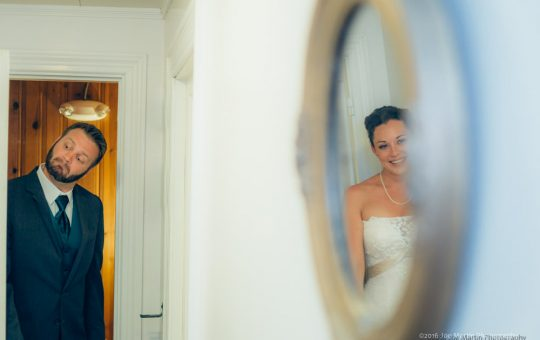 Groom pretending to look around the door at the bride with her in a reflection or a mirror