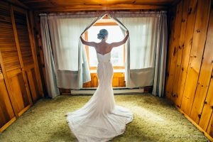 bride opens a window in a wedding portrait