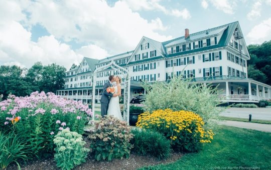 couple poses in front of a New Hampshire Wedding venue in Jackson, NH