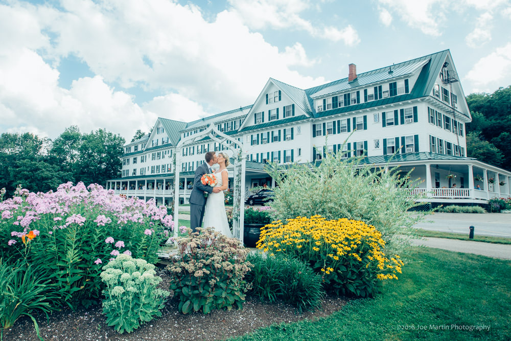 Couple poses for a photos in front of the Eagle Mountain House, A New Hampshire wedding venue
