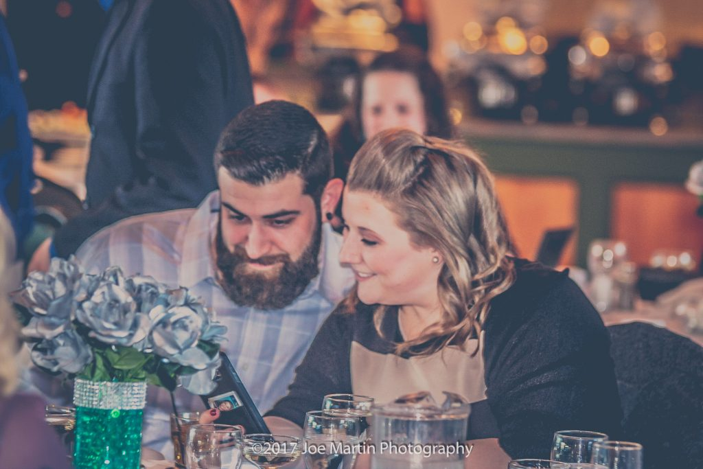 couple looking at their cell phone during wedding reception