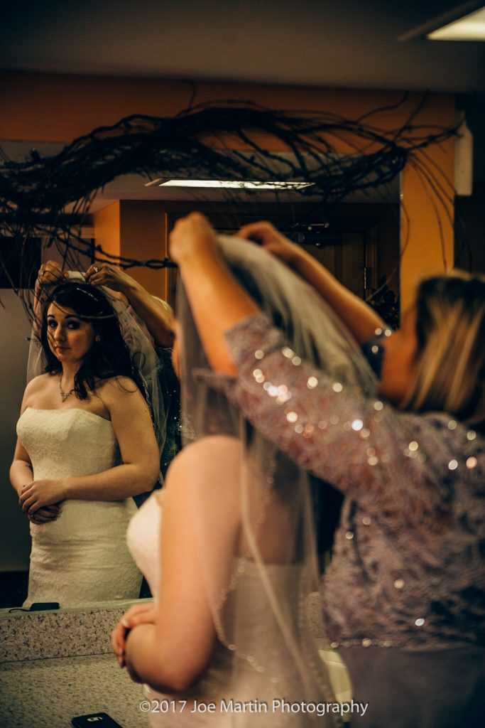 mother helping bride with her vale before the wedding