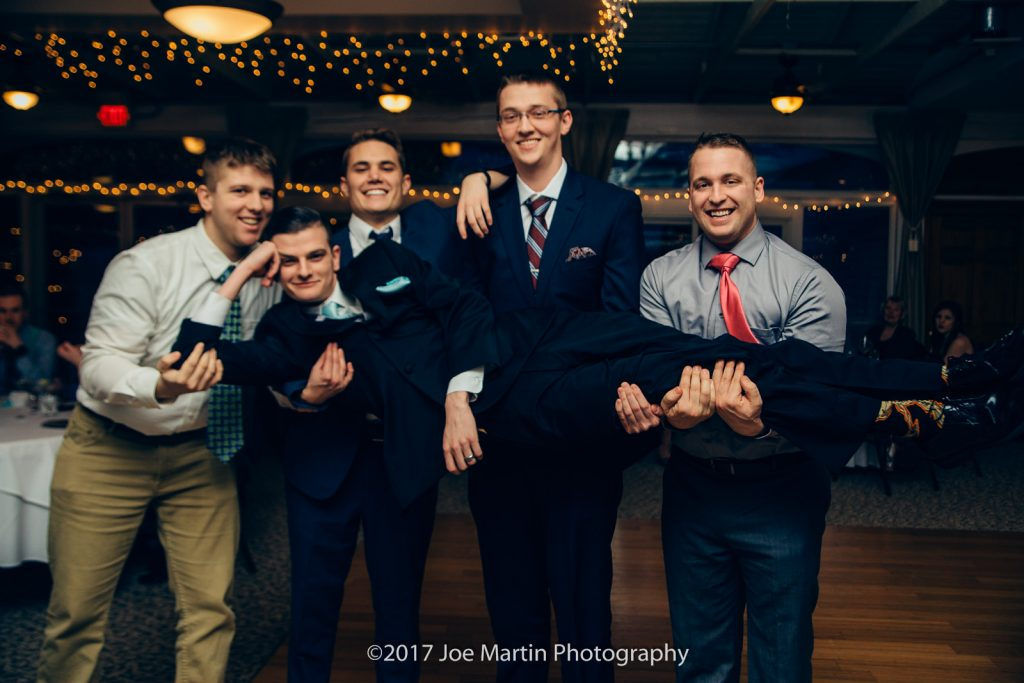 The guys holding the groom in a reception photo