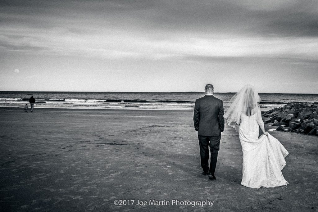 Black and white photo of a couple walking on the beach after the wedding